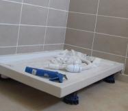 Le bac de douche est surélevé pour faciliter l'écoulement de l'eau.