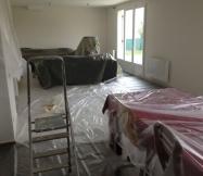 Les meubles du salon sont aussi protégés avant le début des travaux de peinture.