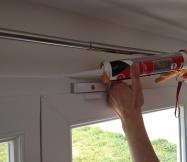 Nous commencons par appliquer le mastic en haut des portes-fenêtres.