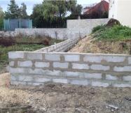 Mur de parpaings en cours de construction.
