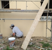 Un ouvrier applique le crépi sur la façade avant de la maison.