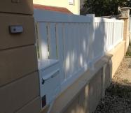 La sonnette est collée sur le pilier et la boite aux lettres est encastrée dans la clôture.