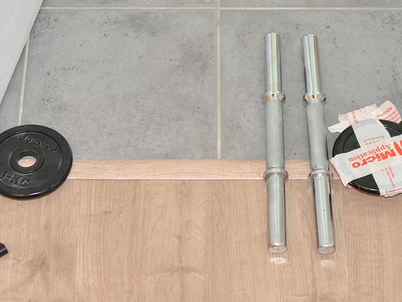 Nous avons posé des poids sur la barre de seuil pour laisser sécher le joint de silicone.