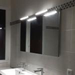 Décoration : pose d'un miroir et d'appliques dans la salle de bain